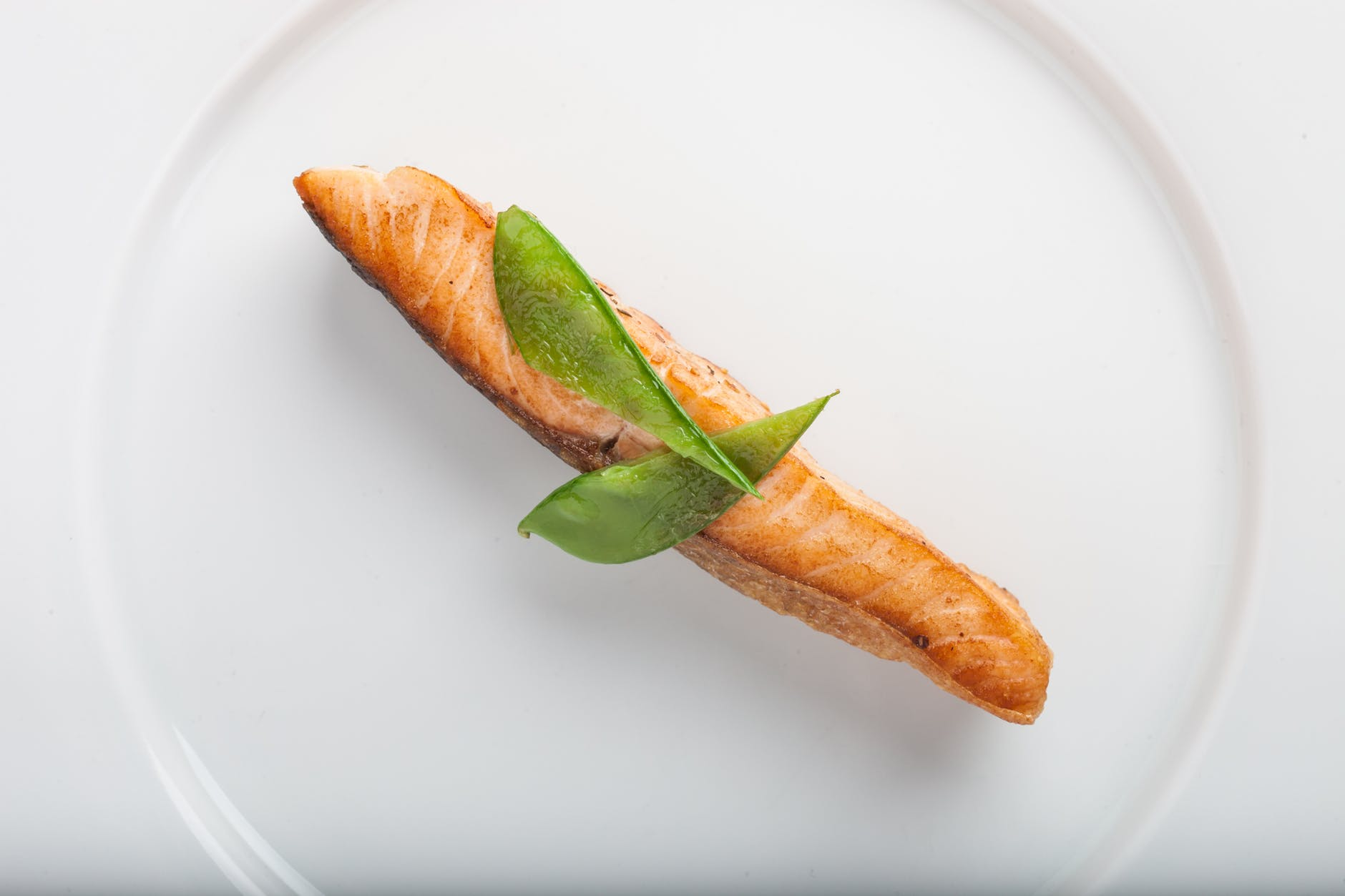 cooked fish with two green leaf on round white ceramic plate